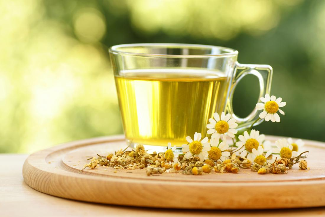A mug of chamomile herbal tea, surrounded by chamomile plants and flowers.