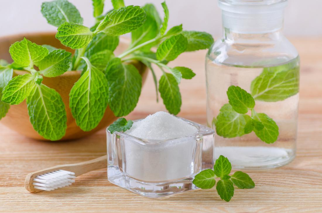 A wooden toothbrush, mint plant, glass pot of salt, and glass bottle of clear liquid, on a wooden table. Ingredients for natural salt mouthwash.