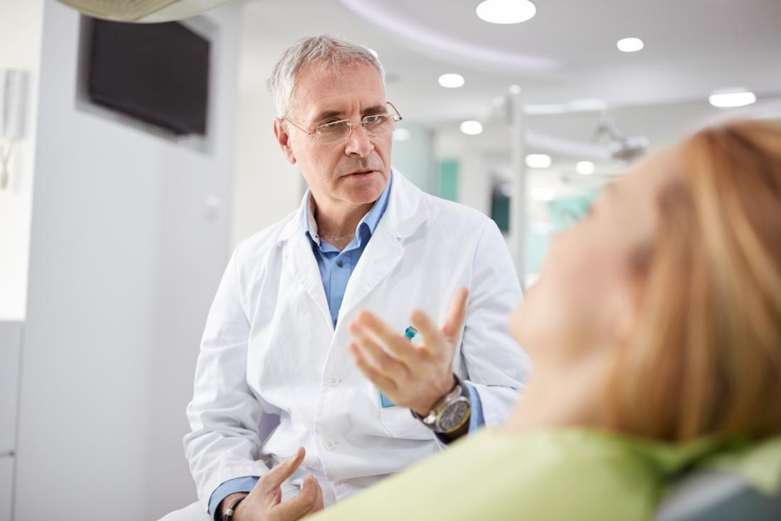Dental surgeon speaking with patient.