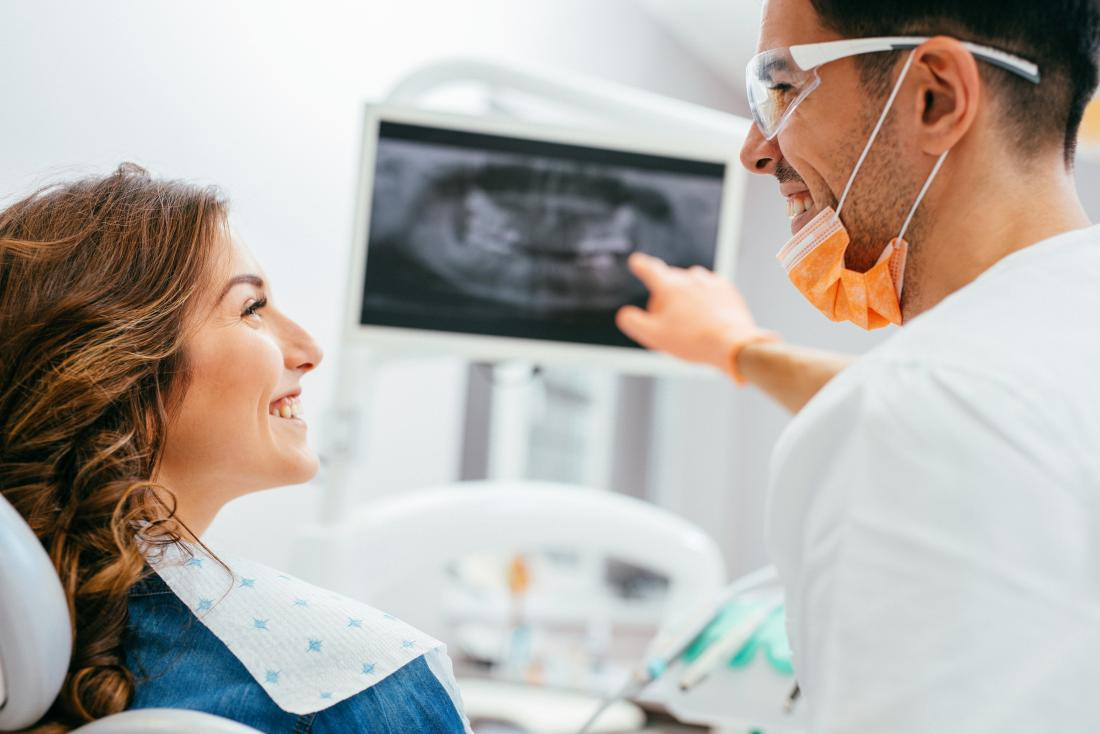 Woman at the dentists looking at an x-ray of her teeth.