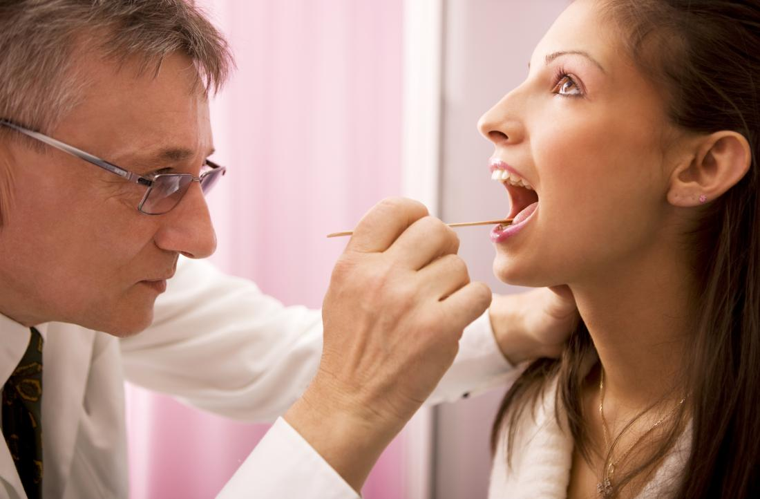 Woman having her tongue and throat inspected by doctor.
