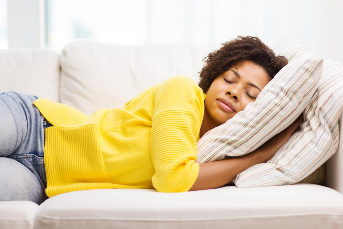 [woman in yellow sweater sleeping on the couch]